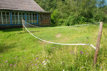 Village volleyball field with overgrown grass and sagging grid