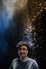 Woman with dark hair in a dark room and flying white powder