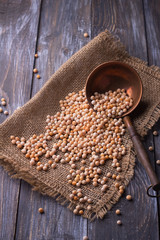 Whole yellow dried peas on sackcloth with a copper spoon, rustic style, selective focus