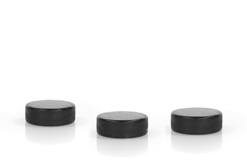 Three hockey pucks on a white background