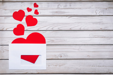 Paper hearts cut from paper. Red hearts in a white envelope. Valentine's Day. Copy space.