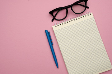 Female styled workplace with glasses, pen and notebook on pastel pink background. Flat lay style, place for text