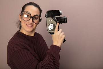 Woman with big glasses holding old film camera
