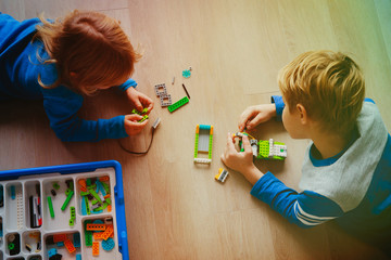 little girl and teenage boy building from colorful plastic blocks