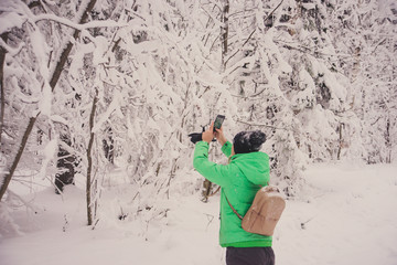 Caucasian young girl tourist with backpack, taking pictures of snow-covered forest in winter for a walk