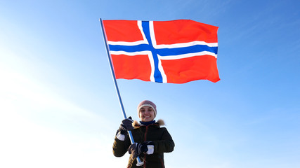 Woman with norway flag on the top point. Succesful winer consept