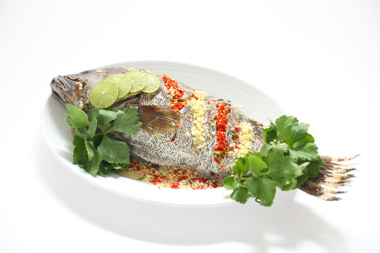 Steamed fish with spicy sauce isolated on white background