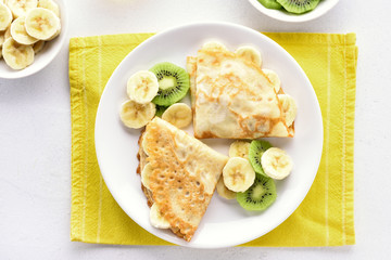 Crepes with banana and kiwi slices