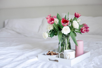 Romantic breakfast in bed. Bouquet of flowers. Roses and tulips. Spring. Valentine's Day. International Women's Day. Cozy.