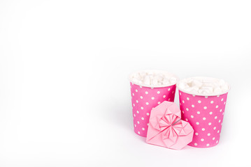 Latte with marshmallow in pink paper cup and valentine card. Copy space. Romantic concept