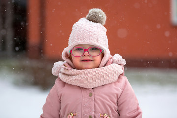 Adorable girl in winter jacket running on the snow