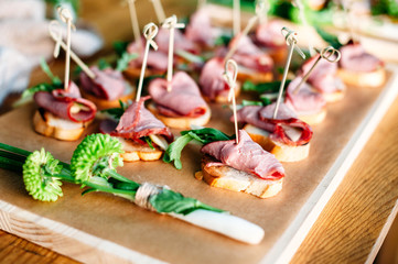 Delicious catering banquet buffet table decorated in rustic style in the garden. Different snacks, sandwiches with ham and greenery on a wooden plate. Outdoor.