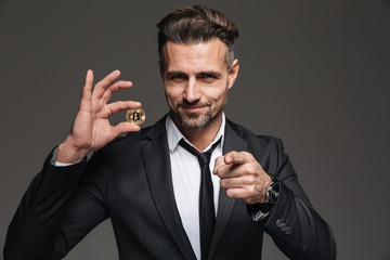 Image of happy male entrepreneur in business suit and tie holding crypto currency and pointing finger on camera, isolated over dark gray wall