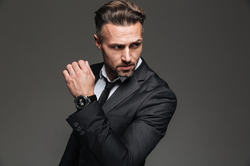 Portrait of handsome serious businessman in black suit looking aside with fancy wrist watch, isolated over white background