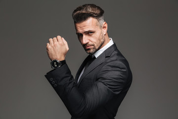 Portrait of handsome rich man 30s in black suit posing on camera with stylish watch on wrist, isolated over graphite background
