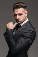 Portrait of rich brunette man 30s in black suit posing on camera with stylish watch on wrist, isolated over graphite background