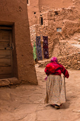 Old berber woman at narrow street of Ait Ben Haddou village, UNESCO world heritage site in Morocco, Africa