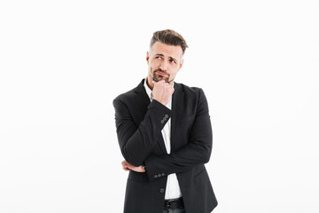 Photo of handsome businessman in suit posing on camera with brooding look and touching his chin, isolated over white background