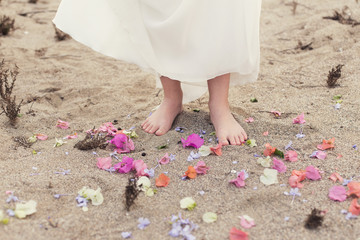Girl standing barefoot in the sand surrounded by flower petals