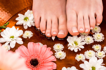 cropped view of woman making spa procedure with flowers for feet