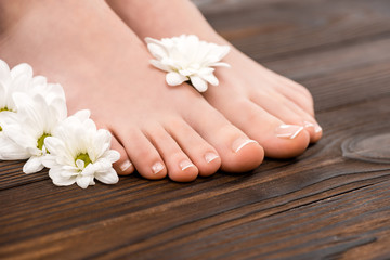 cropped view of feet with natural pedicure and flowers on wooden surface