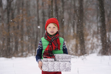 Boy standing in snow carrying Christmas gifts