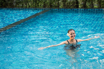 Smiling portrait of beautiful woman in swimming pool,Beautiful young woman relaxing in spa swimming pool.