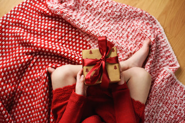 Overhead view of a girl sitting cross-legged holding a wrapped Christmas gift