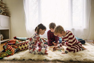 Three children sitting on the floor playing a board game