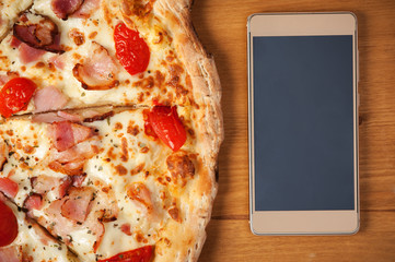 Food delivery concept. Fresh Italian pizza and smartphone on wooden table. Place for text.