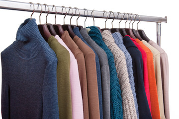 On the hangers hangs a lot of warm jackets and cardigans