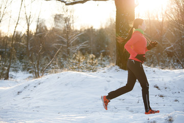 Picture of sports girl on run through winter forest