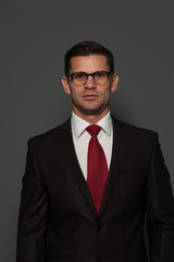 Portrait of successful confident businessman looking at the camera against gray background