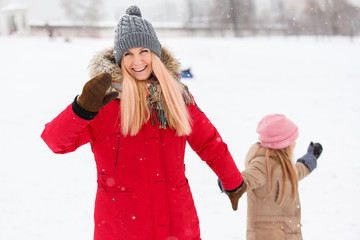 Photo of happy mother and daughter on walk in winter park