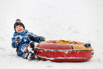 Photo of happy boy with tubing in winter park