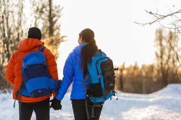 Photo from back of man and woman with backpacks in winter