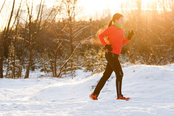Photo of young brunette in sportswear on morning run in winter