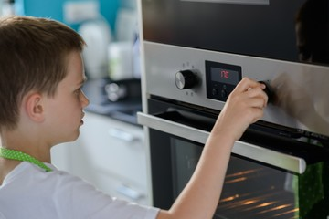 Child boy regulating temperature of the oven.