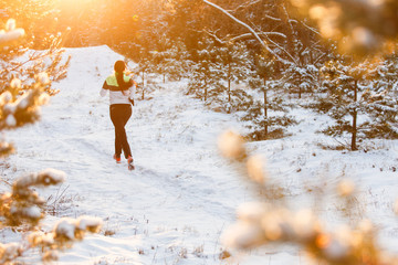 Image from back of sportswoman running through winter forest