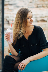Charming young woman drinks milk-shake sitting in a cosy loft cafe