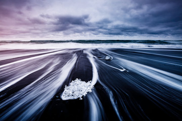 Large pieces of the iceberg that sparkle on the black sand. Location place Jokulsarlon, Vatnajokull national park, Iceland.