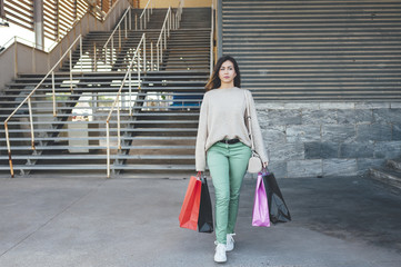 Pretty millennial woman holding shopping bags in shopping area