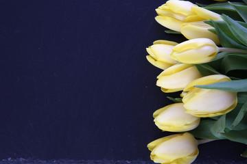 bunte tulpen auf schwarzer schiefersteinplatte