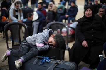 Girl sleeps on a suitcase as she waits with her family for a travel permit to cross into Egypt through the Rafah border crossing after it was opened by Egyptian authorities for humanitarian cases, in the southern Gaza Strip