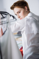 young fashion designer looking at dresses on rack