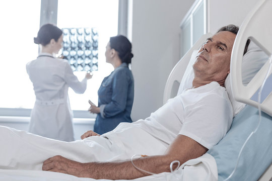 I am so tired. Selective focus on a poor man with a drop counter thinking of something sad while a group of doctors analyzing his MRI scan in the background.