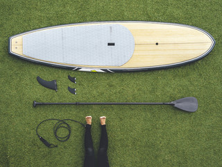 Paddle surf still life, paddle board, keels, row, leash and woman legs on wet suit