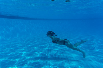 Underwater woman portrait with white bikini in swimming pool. Summer vocation