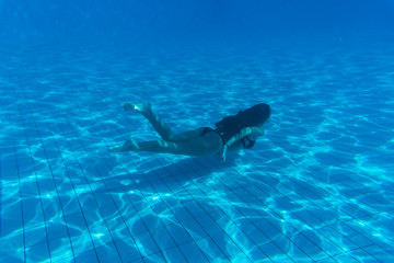 Young woman portrait wearing bikini underwater in swimming pool. Vacation, fun, lifestyle concept.