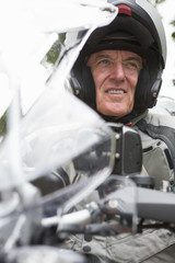 Close up of smiling senior man wearing helmet on motorcycle